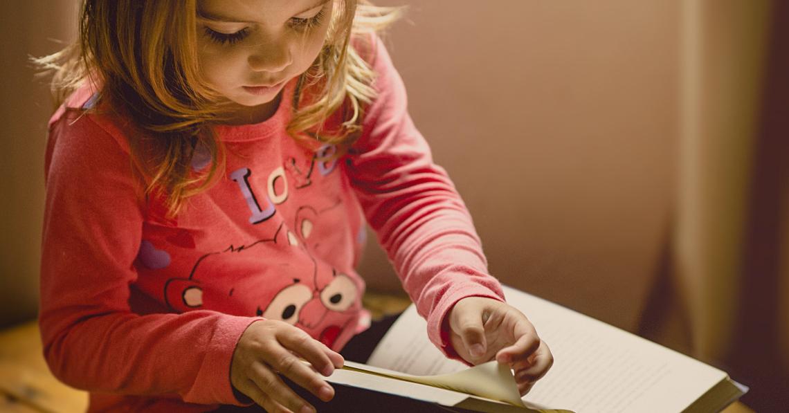 una nena llegint un llibre